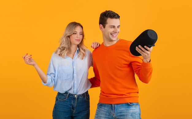 Beautiful smiling young couple holding wireless speaker listening to music dancing on orange