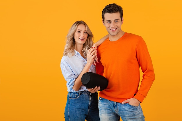 Beautiful smiling young couple holding wireless speaker listening to music
