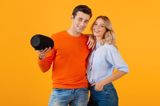 Красивая улыбающаяся молодая пара, держащая беспроводной динамик, слушая музыку в красочном стиле, счастливое настроение, изолированное на желтой стене