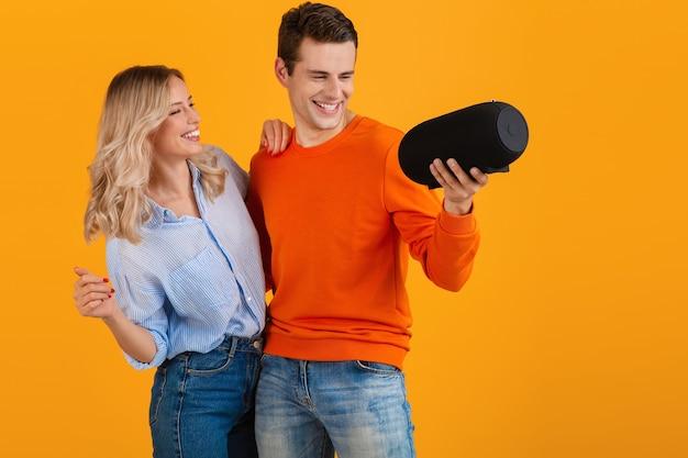 Красивая улыбающаяся молодая пара, держащая беспроводной динамик, слушает музыку, танцует эмоциональную