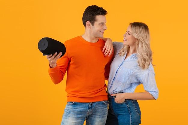 Красивая улыбающаяся молодая пара, держащая беспроводной динамик, слушает музыку