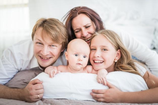 Красивая улыбающаяся молодая семья, мама, папа, старшая дочь и новорожденный ребенок, лежат на большой кровати в яркой спальне