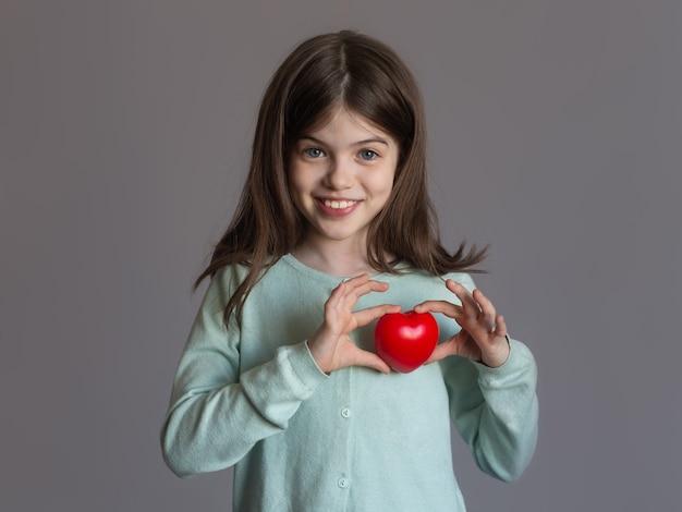 Красивая улыбающаяся молодая девушка держит в руках красное сердце, концепция любви, здоровья