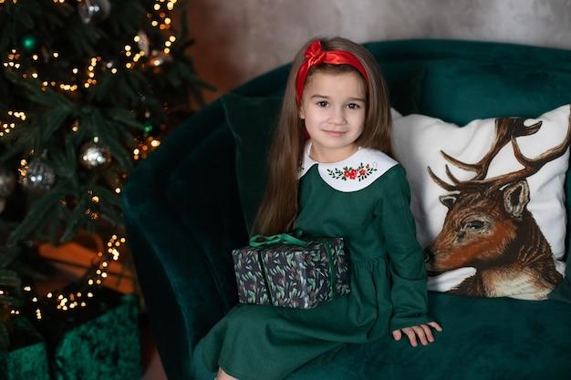 Красивая улыбающаяся молодая девушка сидит с подарком на диване у елки в уютной гостиной