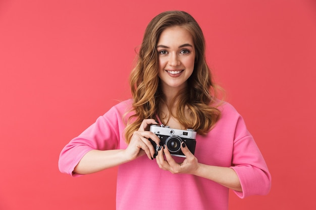 Beautiful smiling young girl wearing casual clothes standing isolated over pink wall, taking picture with photo camera