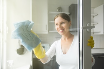 Beautiful smiling young housewife washing the windows