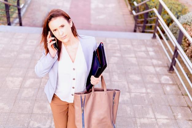 Красивый улыбающийся молодой предприниматель средних лет разговаривает на смартфоне на улице, поднимаясь по лестнице. концепция успешной работы женщины. копировать пространство