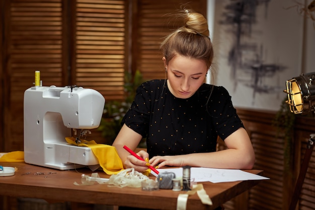 Beautiful smiling young seamstress creates drawings of clothes