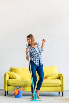 Beautiful smiling young woman cleaning the house singing