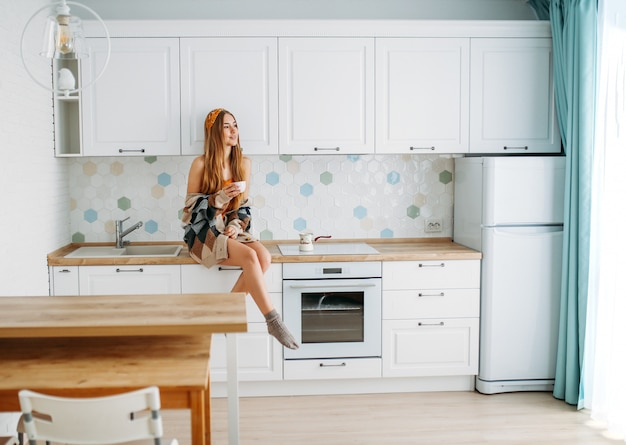 Beautiful smiling young woman fair long hair girl wearing in cozy knitted cardigan with cup of morning cofee sitting on kitchen work surface at home