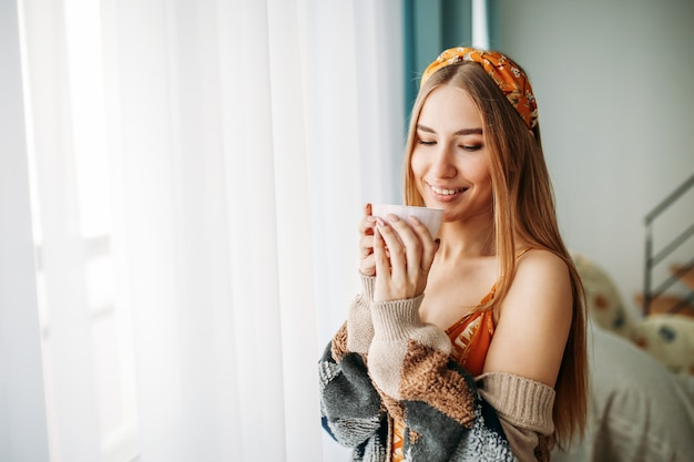 Beautiful smiling young woman fair long hair girl wearing in cozy knitted cardigan with cup of tea near window at home