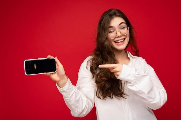 孤立した立っているカジュアルなスタイリッシュな服を着て格好良い美しい笑顔の若い女性