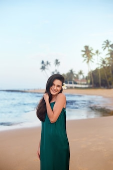 Beautiful smiling young woman in green dress on beach over sea and blue sky background. summer  vacation, travel