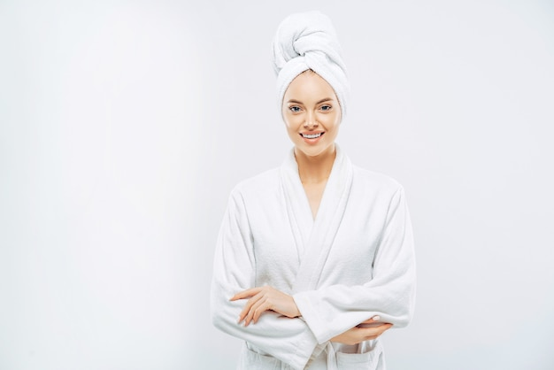 Beautiful smiling young woman has soft healthy skin after taking shower, wears bath robe and towel wrapped on head, enjoys spare time at home, isolated over white wall. wellness concept.