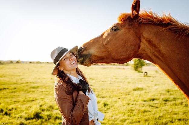 Beautiful smiling young woman in a hat and gloves playing with a broun horse in a field on a sunset