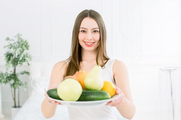 新鮮な果物、リンゴ、梨、レモン、グレープフルーツ、キウイ、キュウリのプレートを保持している美しい笑顔の若い女性。健康的な食事、美容のコンセプト