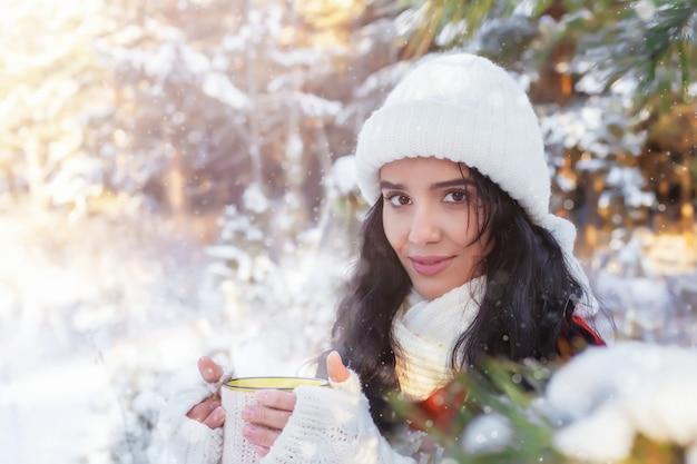 아름다운 미소를 짓고 있는 젊은 여성은 겨울 숲의 화창한 날 따뜻한 음료가 담긴 머그를 손에 들고 눈, 크리스마스 또는 새해 휴일, 겨울 방학