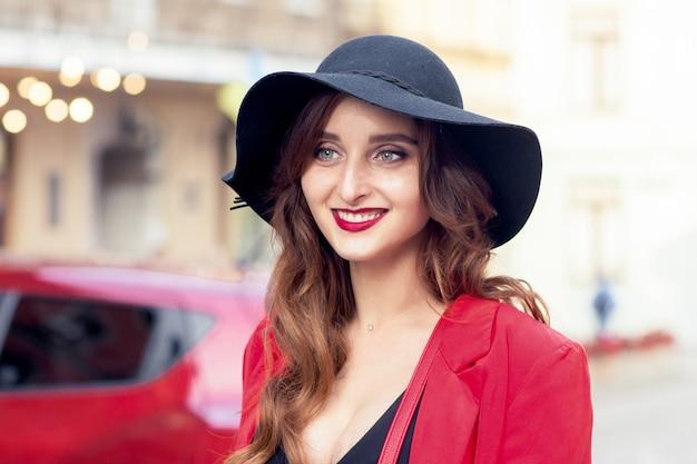 검은 모자에 아름 다운 웃는 젊은 여자
