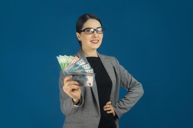 Красивая улыбающаяся молодая женщина в очках и сером пиджаке с тенге в ваших руках на синем фоне