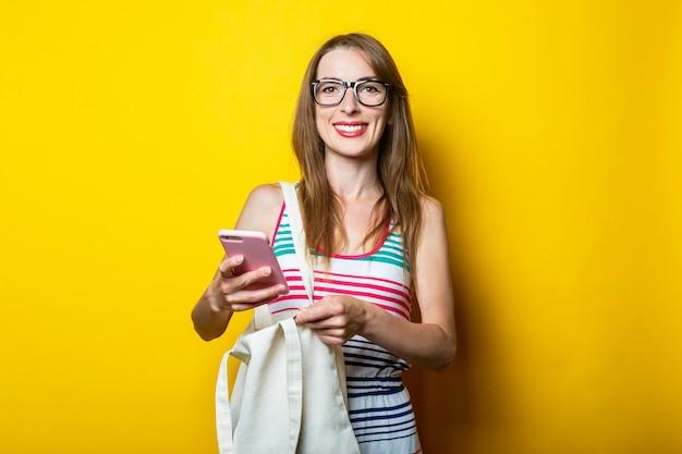 노란색 바탕에 전화를 들고 린 넨 가방 안경에 아름 다운 미소 젊은 여자.