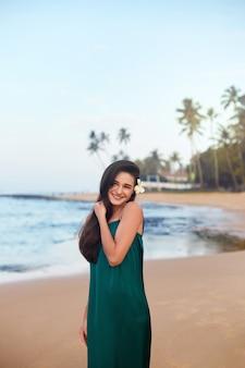 海と青い空を背景にビーチで緑のドレスの美しい笑顔の若い女性。夏休み、旅行