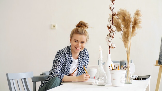Beautiful smiling young woman is sitting at a table and writing plans on paper with a pencil
