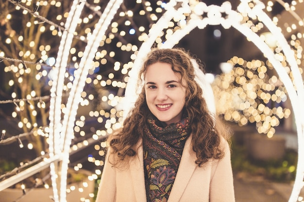Beautiful smiling young woman outdoors with lights