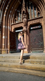Beautiful smiling young woman posing on old stone stairs against catholic cathedral at old town
