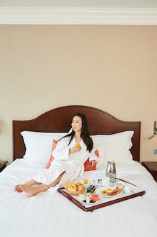Beautiful smiling young woman relaxing on bed in bathrobe, drinking fresh orange juice and eating breakfast