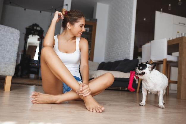 Bella giovane donna sorridente che si siede a gambe accavallate sul pavimento in salone che esamina da parte il bulldog francese allegro.