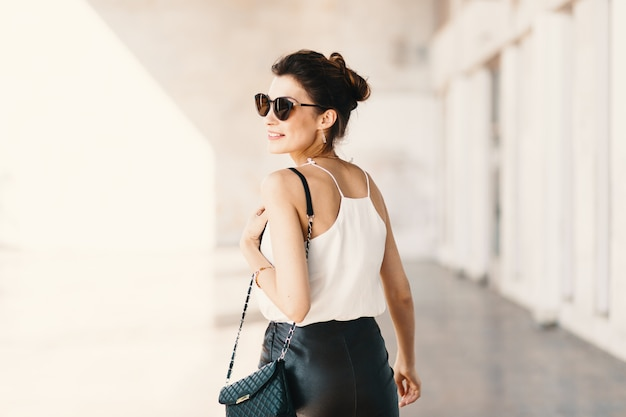 Beautiful smiling young woman in sunglasses looking away over th