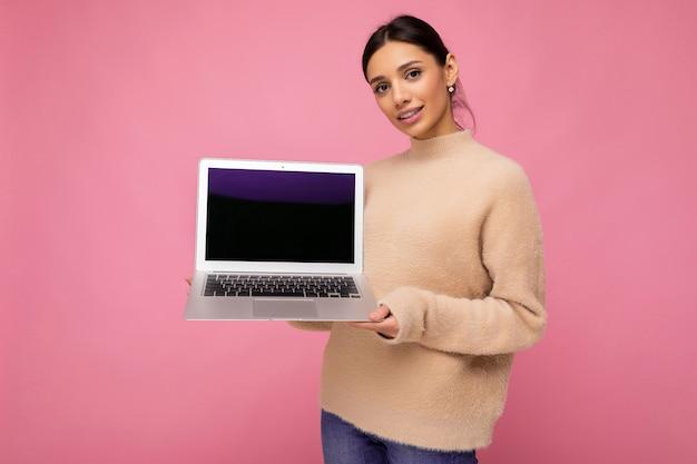 Красивая улыбающаяся молодая женщина с темными волосами, смотрящая в камеру, держа компьютерный ноутбук с пустым