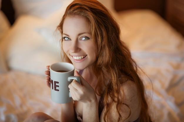 自然なメイクアップと長いまつげの美しい笑顔の若い女性は、ホットコーヒーまたは紅茶のカップを保持しています。冬のシーズン。