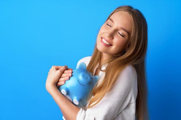 Красивая улыбающаяся молодая женщина с копилкой на синем фоне