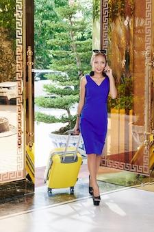 高級ホテルに入るときに電話で話している小さなスーツケースを持つ美しい笑顔の若い女性