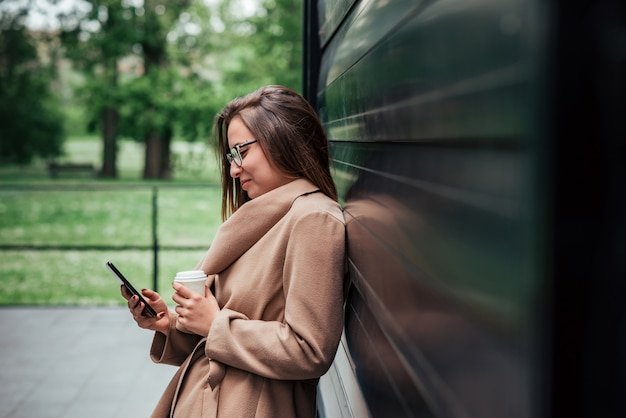 Beautiful smiling young woman with takeaway coffee using smart phone while leaning on a wall outdoors.