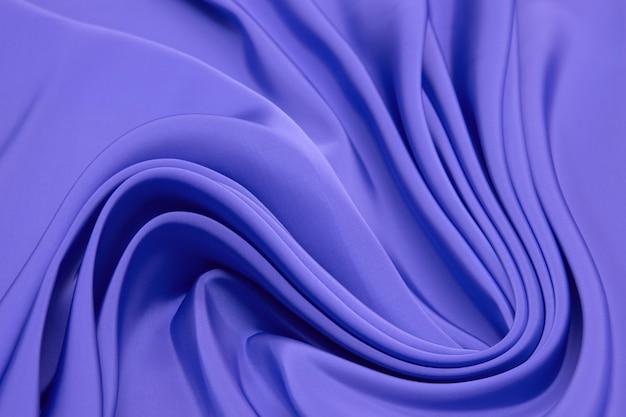 Красивая гладкая элегантная волнистая фиолетовая или фиолетовая текстура ткани, абстрактный фон