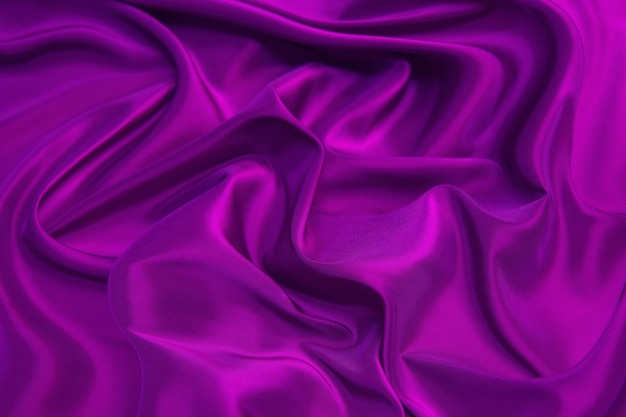 Beautiful smooth elegant wavy violet or purple fabric texture, abstract background for design.