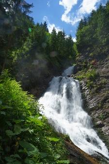 Красивый ровный водопад в окружении зелени, травы и лесных фьордов