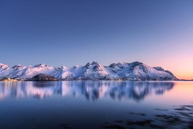 美しい雪に覆われた山々とカラフルな空が夜に水に反映