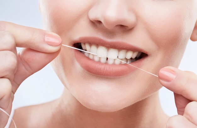 Beautiful snow-white smile. ideal strong white teeth, teethcare. healthcare, stomatological concept for dentists. only smile, cleaning teeth with tooth thread