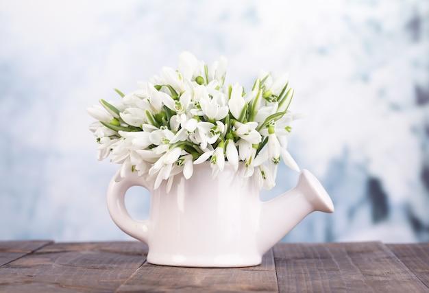 Красивые подснежники в вазе, на столе на яркой поверхности