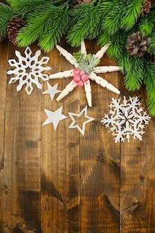 Красивые снежинки с еловой веткой на деревянных фоне