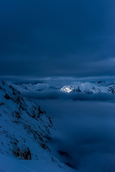 Beautiful snowy hills and mountains at night with breathtaking cloudy sky