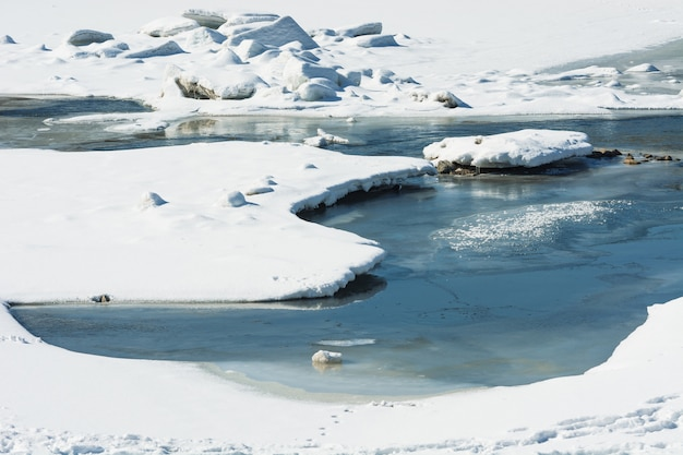 Beautiful snowy landscape with river is covered ice. frozen river during thaw.