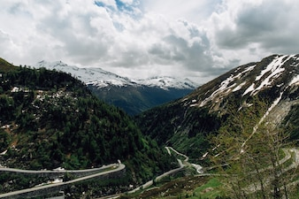 Beautiful snowy Swiss Alps mountains and curve track in summer time