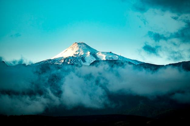 Красивая снежная вершина вулканических гор с голубым небом и облаками вокруг