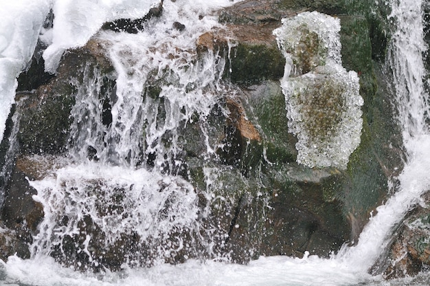 Красивый снежный водопад, протекающий в горах