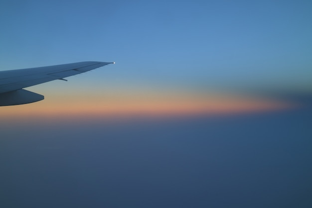 Beautiful soft color of sunrise sky with airplane wing, background with copy space