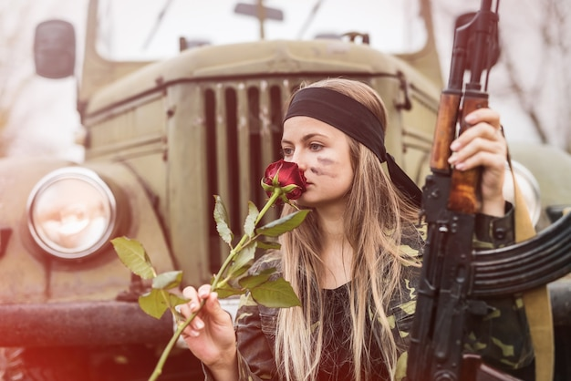 Beautiful soldier with rose flower and rifle